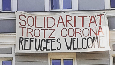 Banner an einer Hauswand Solidarität trotz Corona Refugees welcome