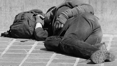 Obdachloser Mann schläft auf der Straße, sein Rucksack liegt neben seinem Kopf