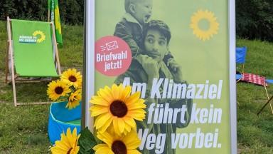 """Aufsteller mit Plakat (""""Am Klimaziel führt kein Weg vorbei."""") dekoriert mit Sonnenblumen."""